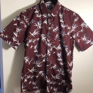 A causal button up t-shirt with leaves print.